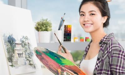 Student artist smiling with paint brush and paint palette